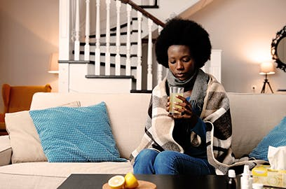 A woman is sitting on the sofa wrapped in a blanket drinking a drink from a glass