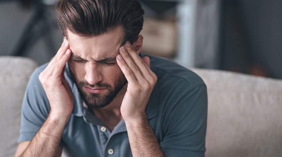 A man is sitting and holding his hands to his head in pain