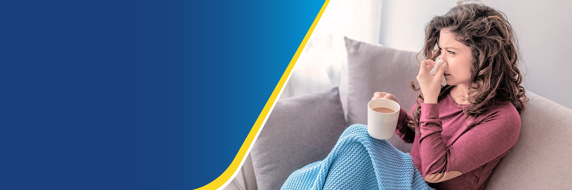A woman is sitting on a sofa under a blanket holding a cup of tea and a tissue to her nose.
