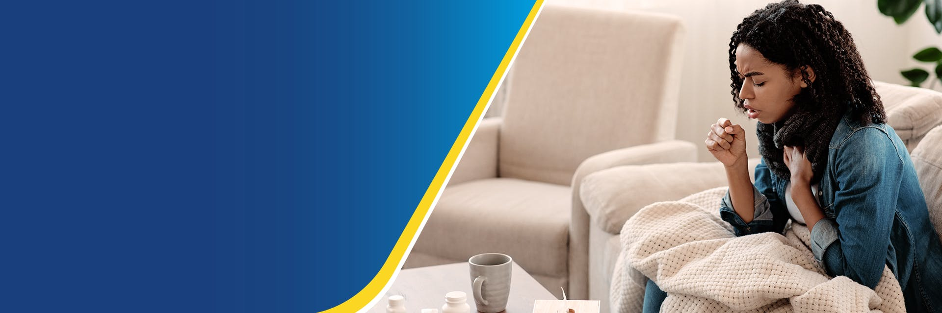 A woman is sitting on a sofa with a blanket on her lap. She is coughing into her hand