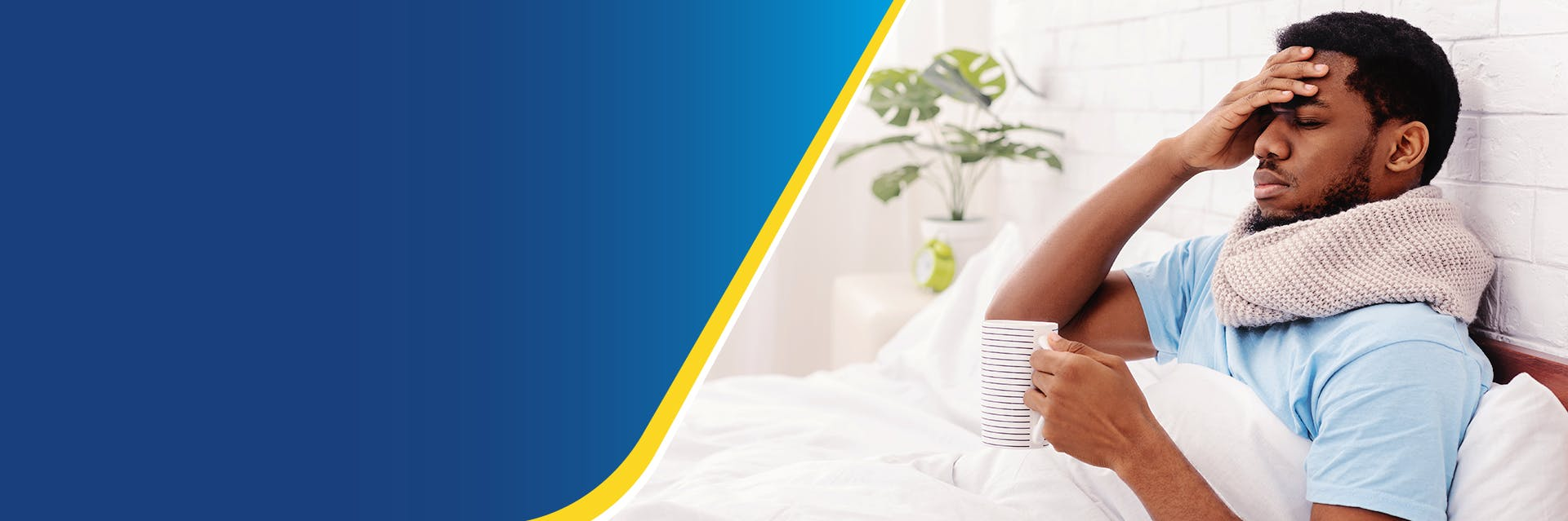 A man in bed is holding a mug and has a hand to his forehead