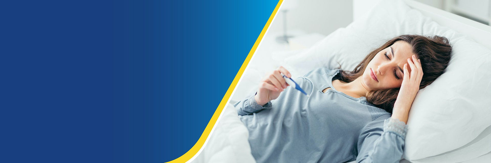 Young woman with flu lying in bed reading a thermometer