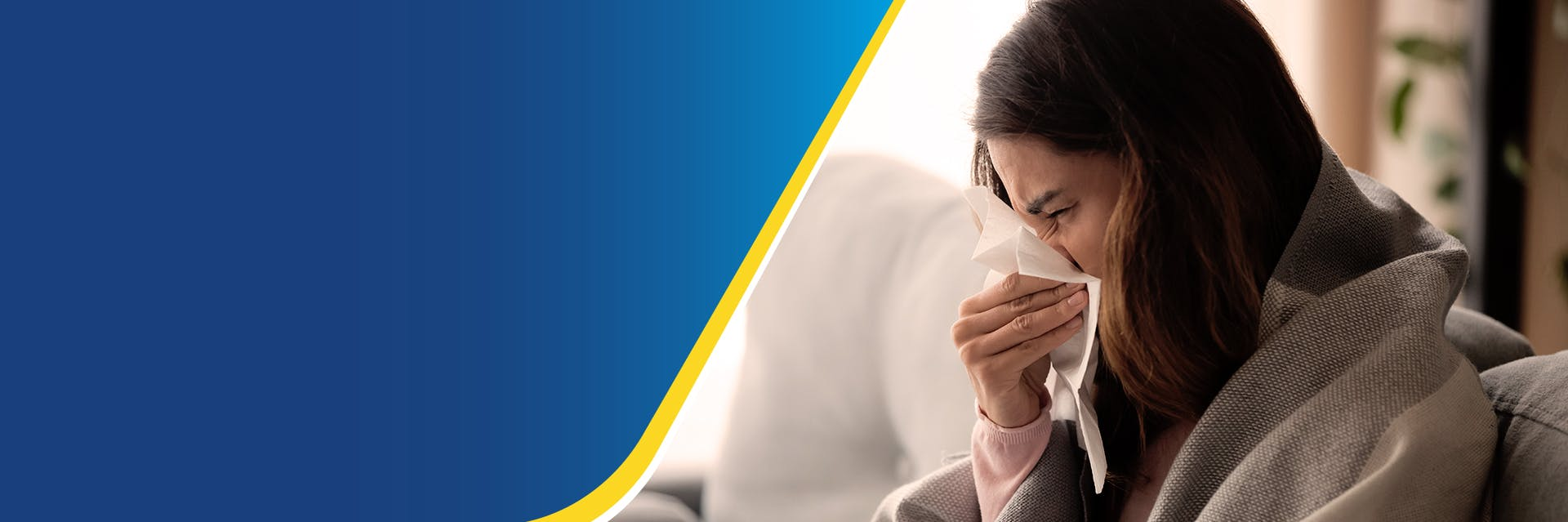 Woman sneezing into tissue with blanket around her shoulders