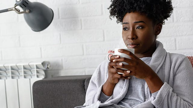 Woman in a robe sipping a mug of hot tea and holding it with both hands