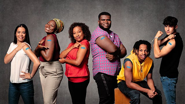 Group of men and women smiling and showing their arms with band aids