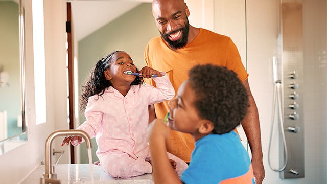 A man is with his 2 children in the bathroom, they are brushing their teeth