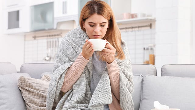 Woman drinking hot beverage at home