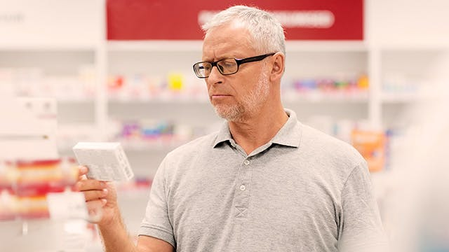 medicine, pharmaceutics, healthcare and people concept -senior male customer with drug at pharmacy