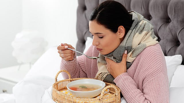 A woman is sitting in bed eating soup
