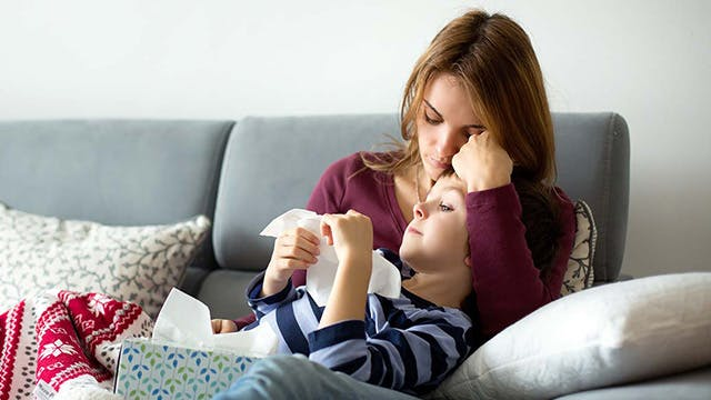 Child with fever being taken care of by mother