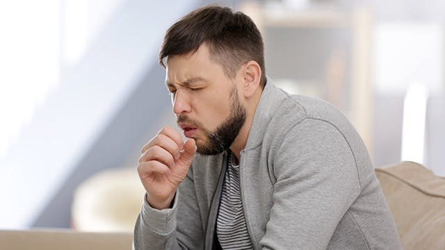 man coughing into fist outside