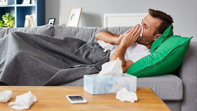 Man with a cold blowing nose into a tissue