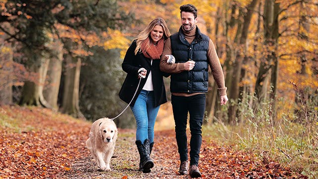 A man and woman are walking down a forest path with a dog on a leash