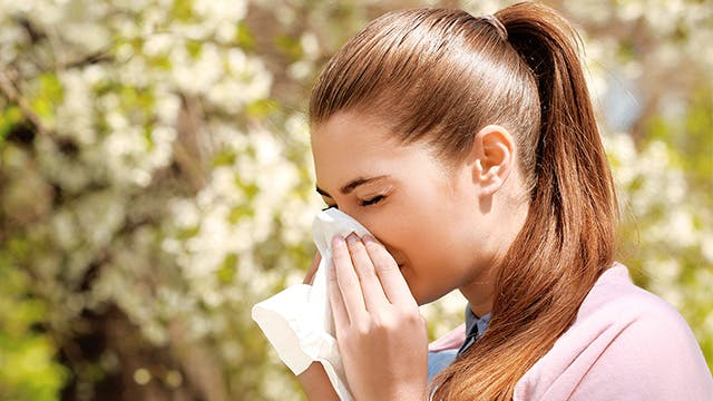 A woman is outside during the spring and is blowing her nose