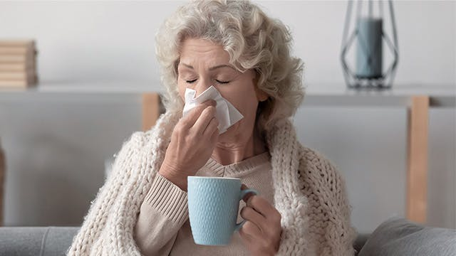 An older woman wrapped in a blanket is sitting on the sofa blowing her nose and holding a mug