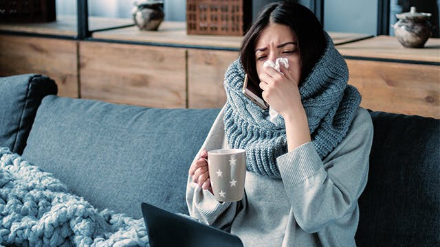 Sick women wearing scarf blows nose on couch