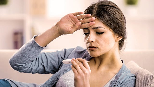 Woman holding her hand to her forehead and looking at a thermometer