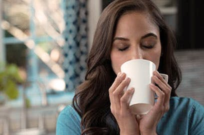 Woman closing her eyes drinking from a mug that she's holding with two hands