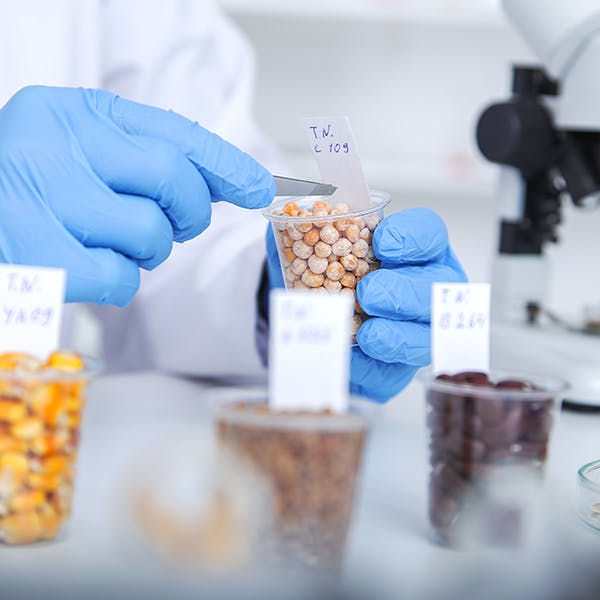 Person in a lab coat measuring ingredients