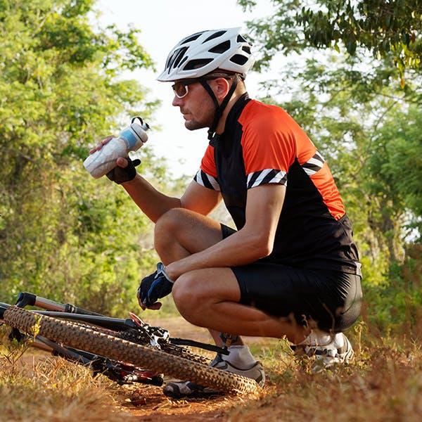 Man drinking water while crouching near bicycle.