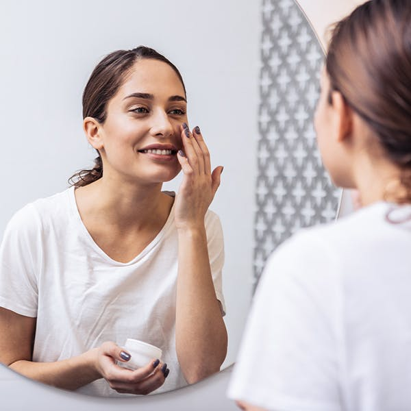 Woman looking in the mirror to apply lotion.