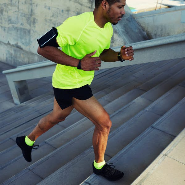 Athletic man running up stairs.