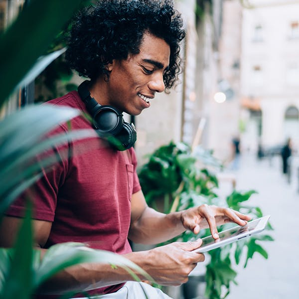 Man wearing headphones using a digital tablet.