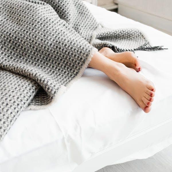 Feet under grey blanket in bed.