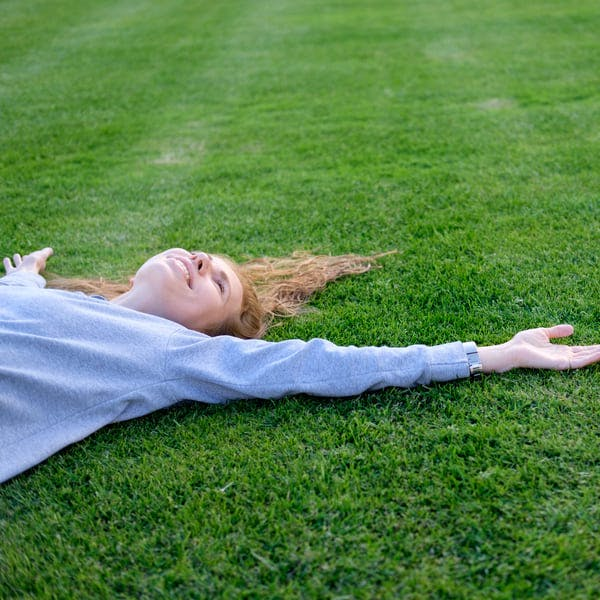 Woman relaxing in a field of grass.