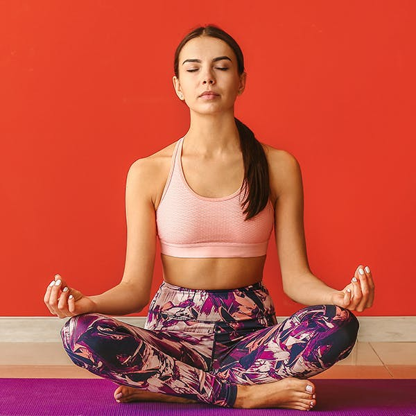 Woman sitting in a meditative pose.