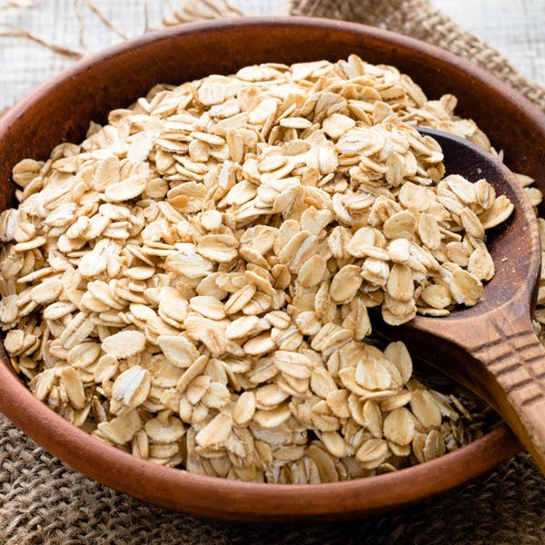 A bowl of oats with a serving sppon.