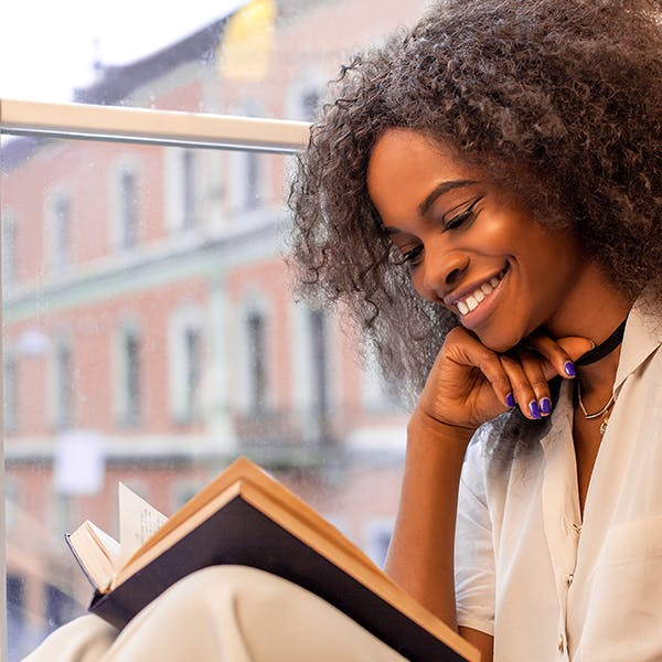 Happy woman reading a book next to a window.