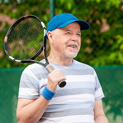 Middle age man playing tennis.