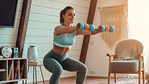 Woman doing squat exercises with weights