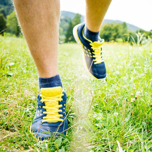 Man walking through grass in colorful sneakers