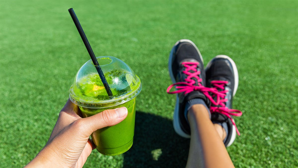 woman drinking green smoothie
