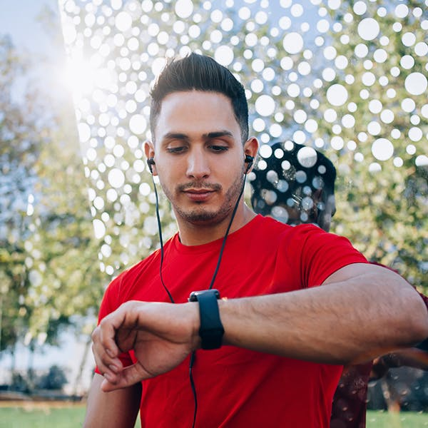 Man with headphones in checking his watch