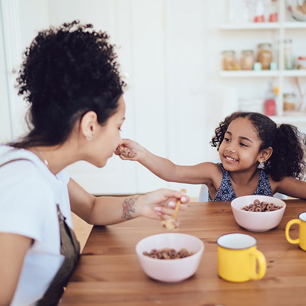 Woman and her daughter eating breakfast cereal together