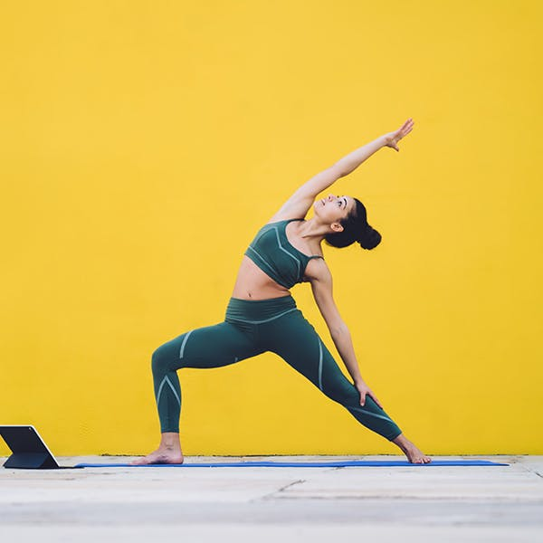 Woman doing yoga stretches in exercises clothes on a yellow background