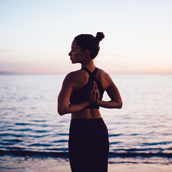 Woman stretching with her hands behind her back at the beach