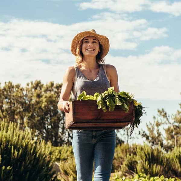 Mujer sujetando una cesta con producto verde