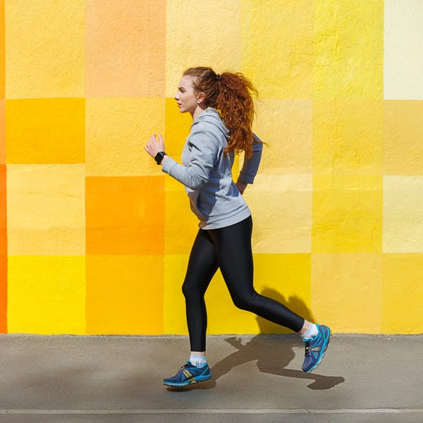 Side view of female athlete running against bright colorful wall