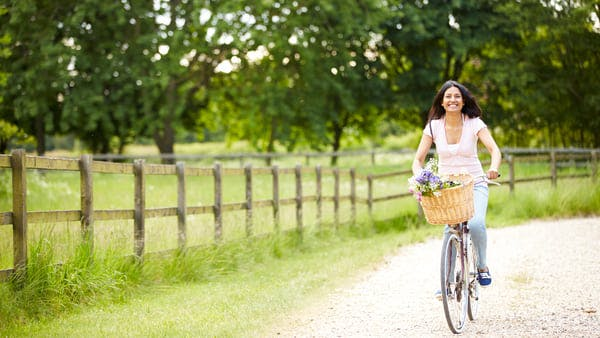 young woman riding a bicycle carrying flowers in the front basket while on country road