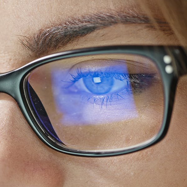 Close up of someone's eye and glasses with computer screen glare