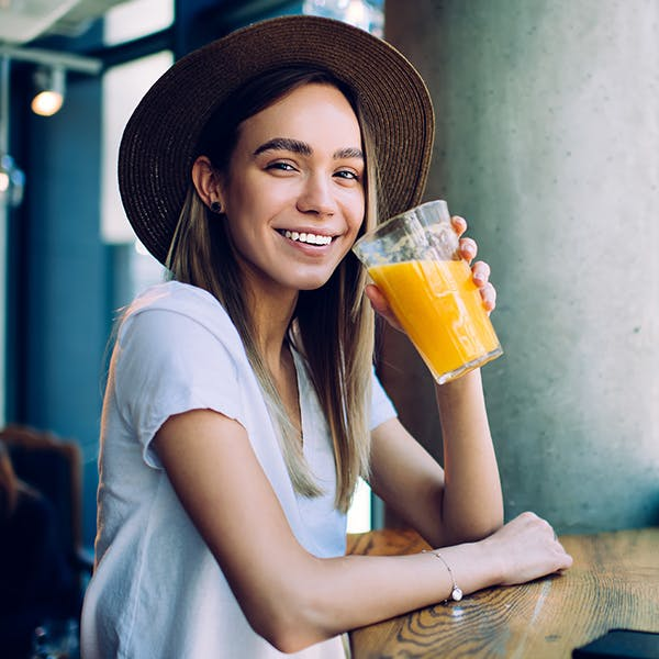 Smiling woman with a hat on drinking an orange drink