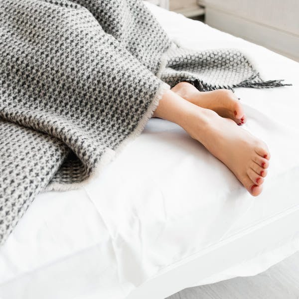 Feet under grey blanket in bed