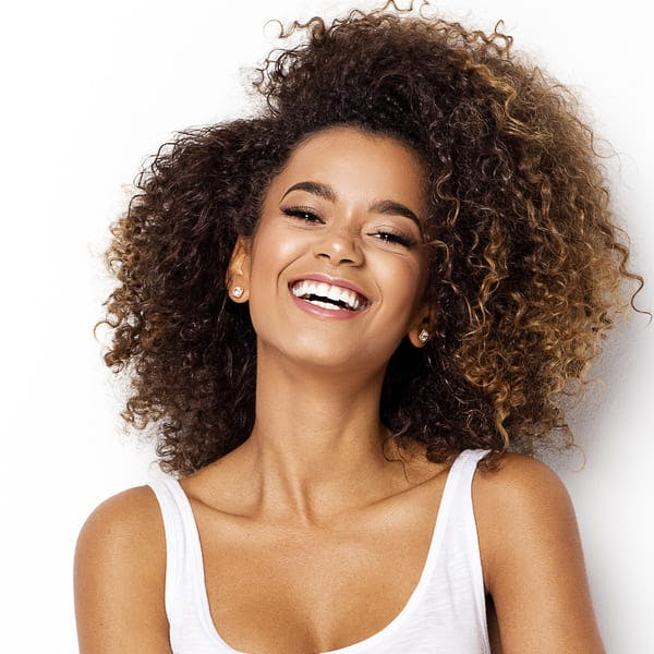 Happy beautiful woman smiling against blank background