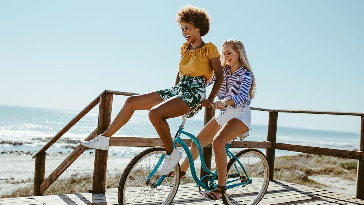 Two women riding a bike by the beach