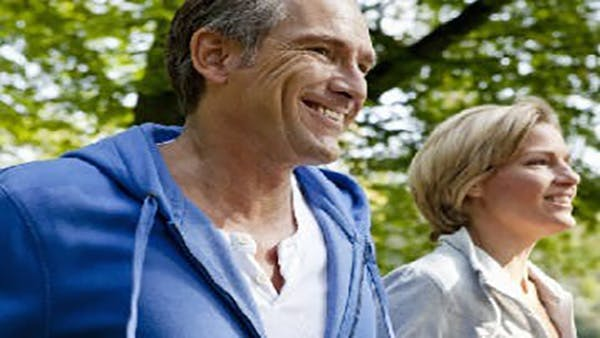 middle aged couple in sweatshirts smiling while outdoors