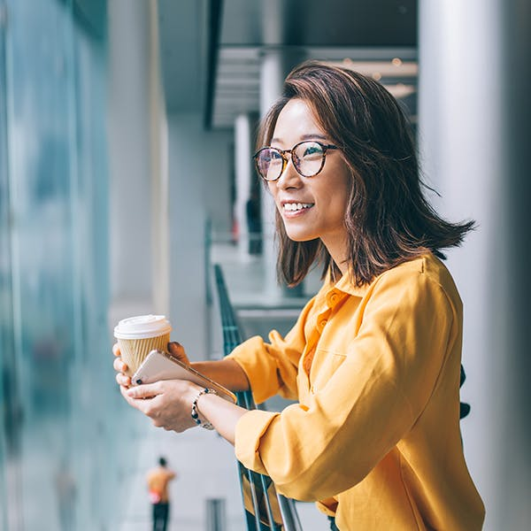 Smiling woman holding a coffee cup looking outside